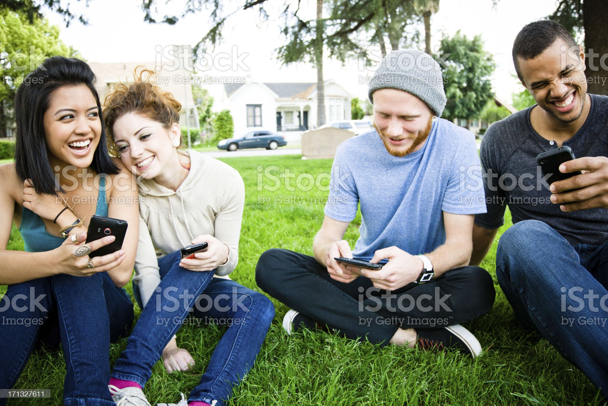 group of teens texting and laughing at park royalty-free stock photo