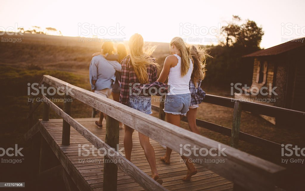 Group of teens walking together at sunset with sun flare stock photo