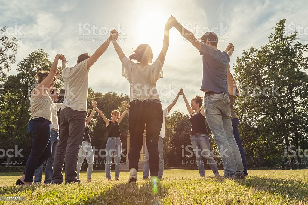 Group of ten friends at the park holding hands stock photo