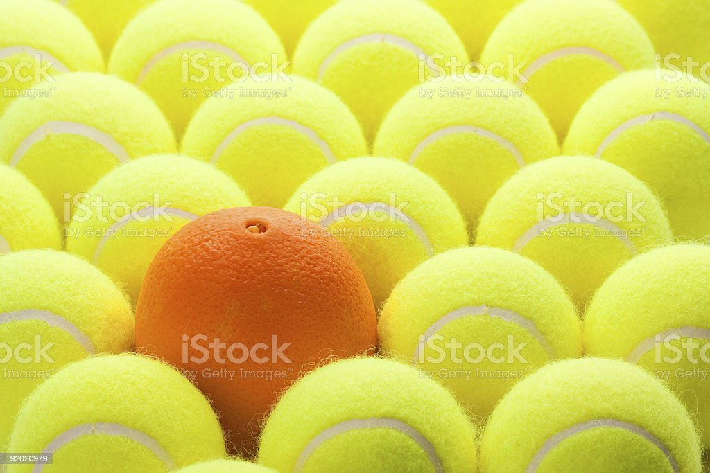Group of Tennis Balls and One Orange royalty-free stock photo