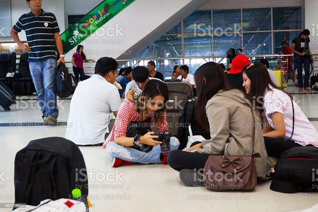 Group of thai sitting on floor of bus terminal stock photo
