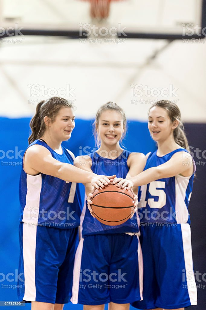 Group of three female high school basketball players standing together stock photo