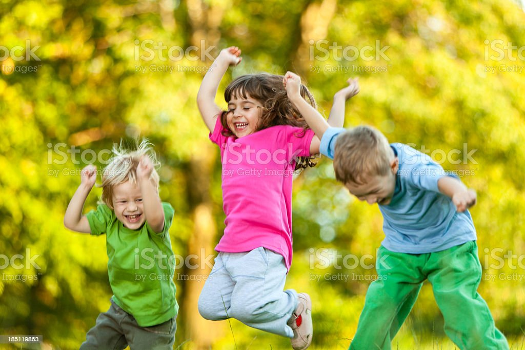Group of three happy children jumping outdoors stock photo