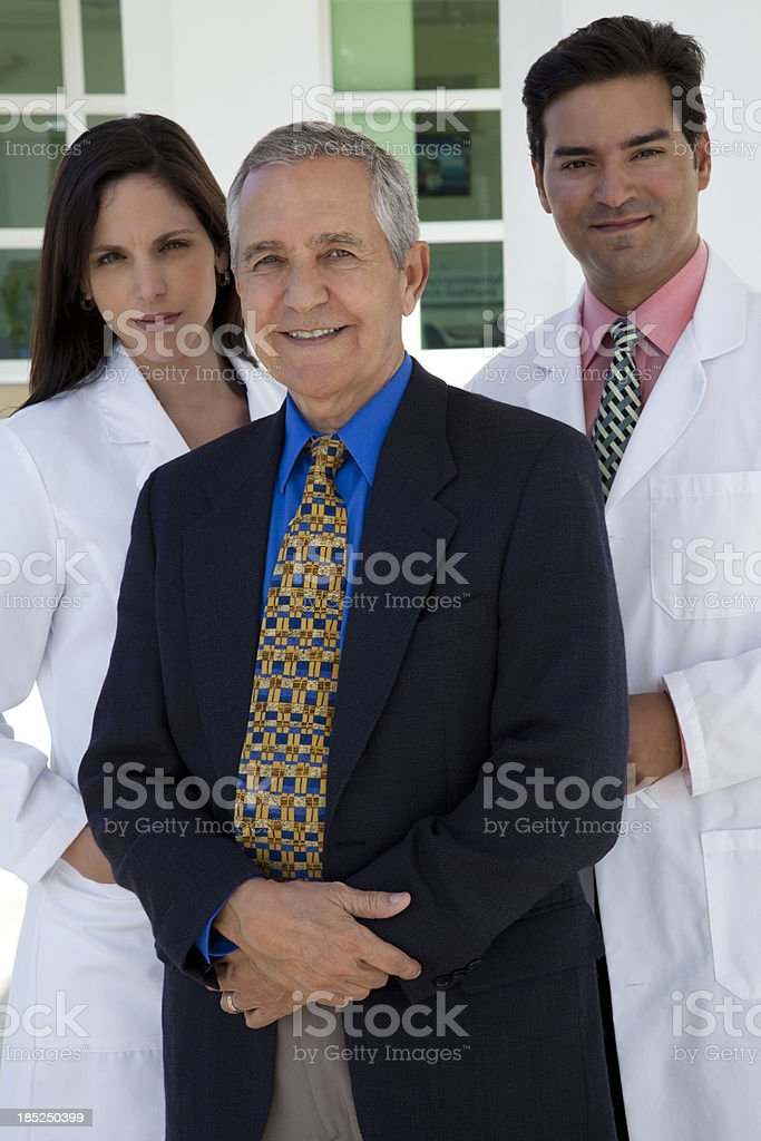 Group of three people, senior businessman, female and male doctors stock photo
