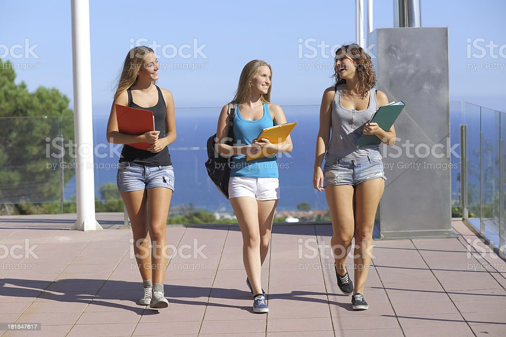 Group of three student teenagers walking towards camera royalty-free stock photo