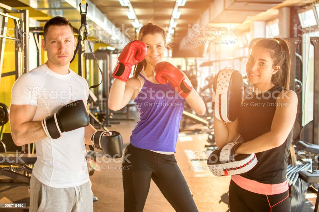 Group of three young people with boxing gloves posing together in gym. stock photo