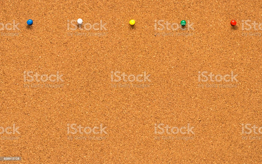 Group of thumbtacks pinned on corkboard stock photo