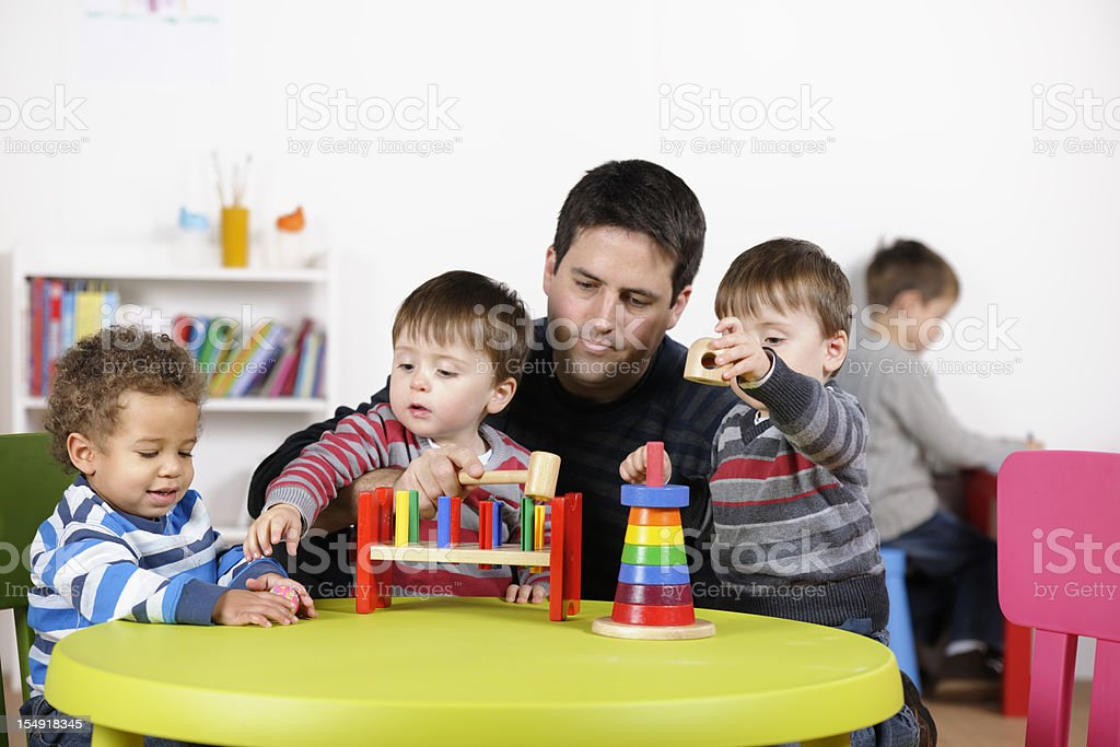 Group Of Toddlers Being Supervised Playing With Multi-coloured Wooden Toys stock photo