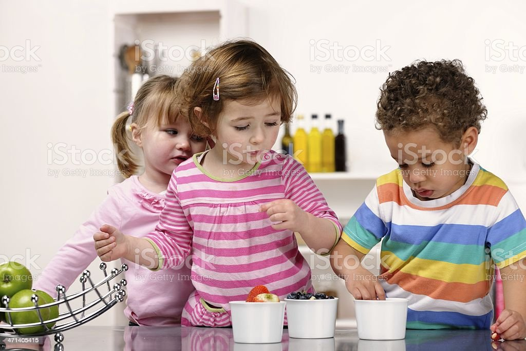 Group Of Toddlers Choosing Fruit In the Kitchen royalty-free stock photo