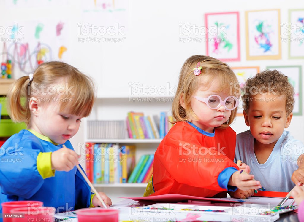 Group Of Toddlers Painting In A Nursery Setting stock photo