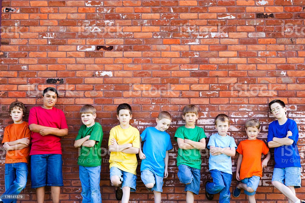 Group of Tough Young Boys Leaning on a Brick Wall stock photo