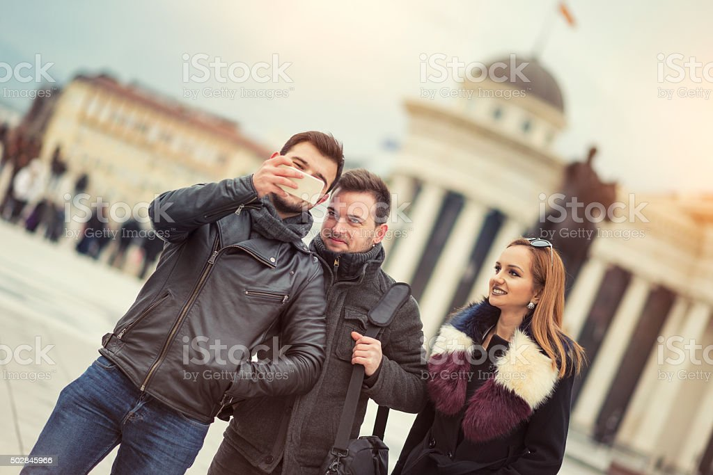 Group Of Tourists Taking Photos with Smartphone at City Street stock photo