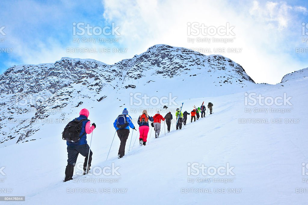Group of tourists to climb on a snowy mountain pass stock photo