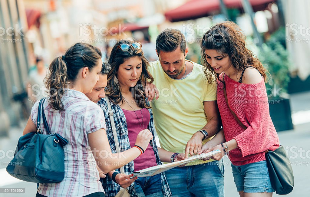 group of tourists using map in the city stock photo