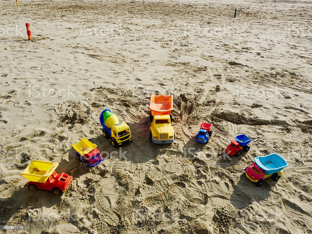 Group of toy working trucks on the beach stock photo