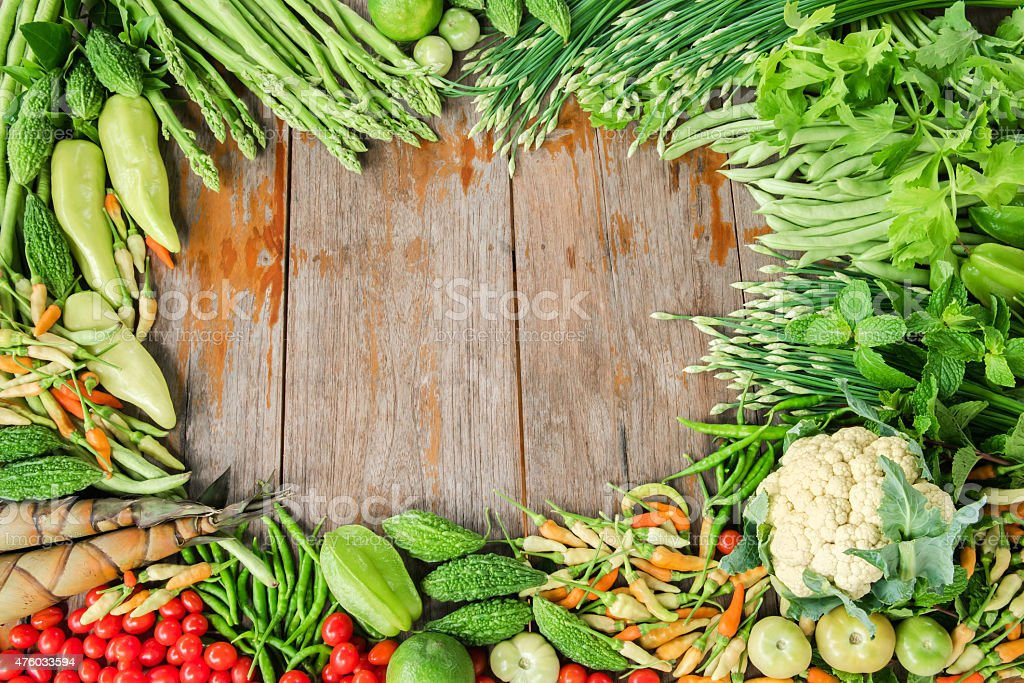 Group of tropical vegetables frame on plank stock photo