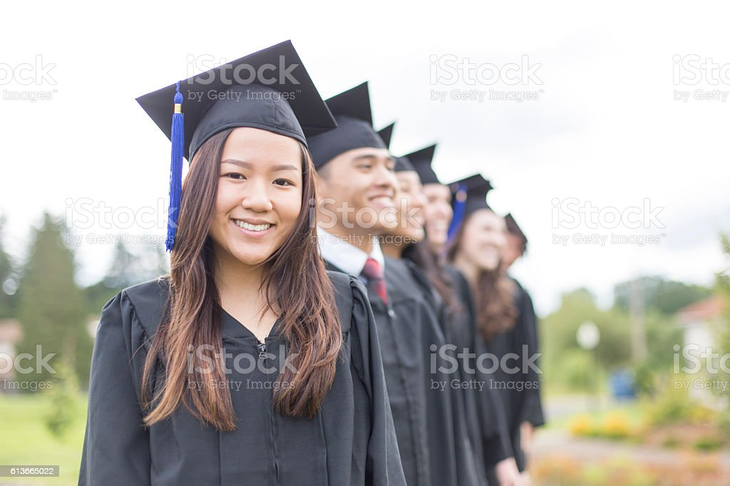 Group of university students wearing graduation gowns stock photo