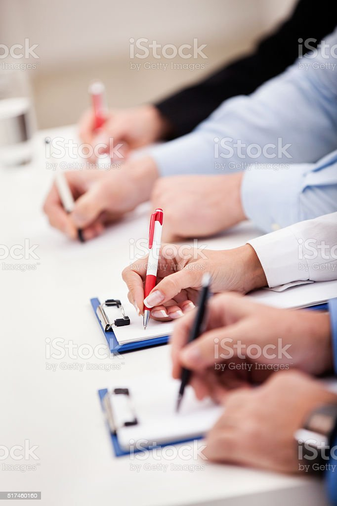 Group of unrecognizable business people writing on a meeting. stock photo
