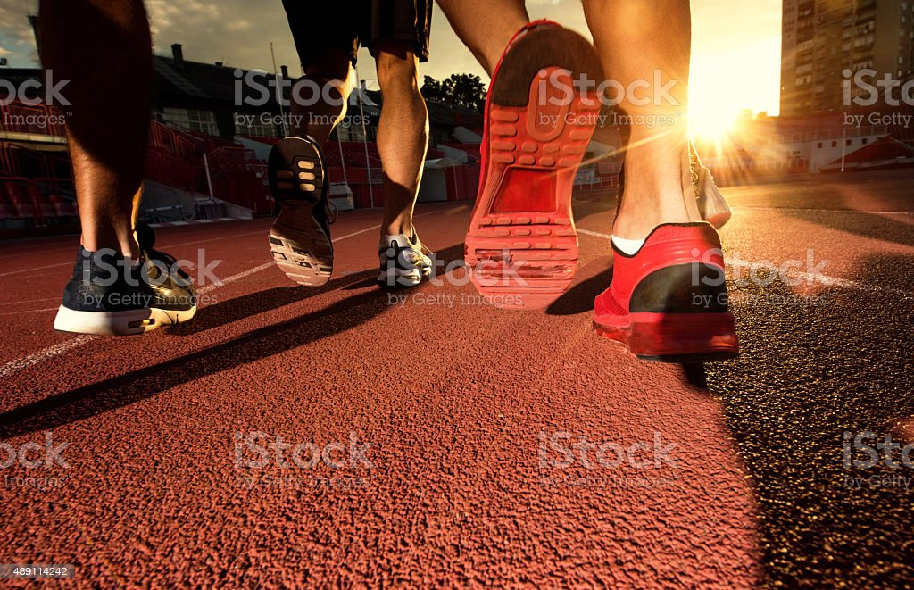 Group of unrecognizable men running a sports race at sunset. stock photo