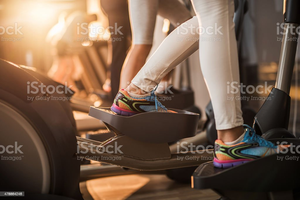 Group of unrecognizable people exercising on cross trainer. stock photo