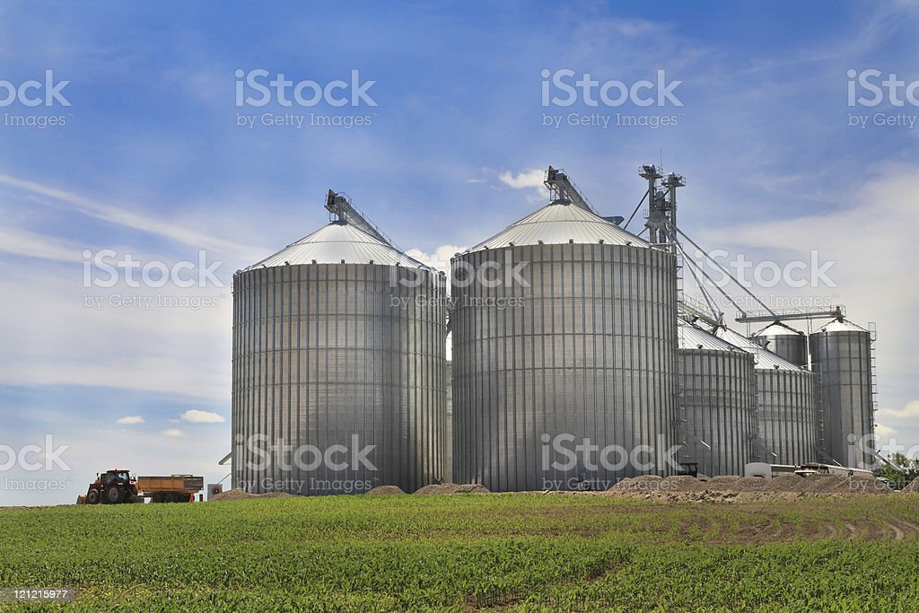 Group of very large steel silos with tractor pulling away stock photo