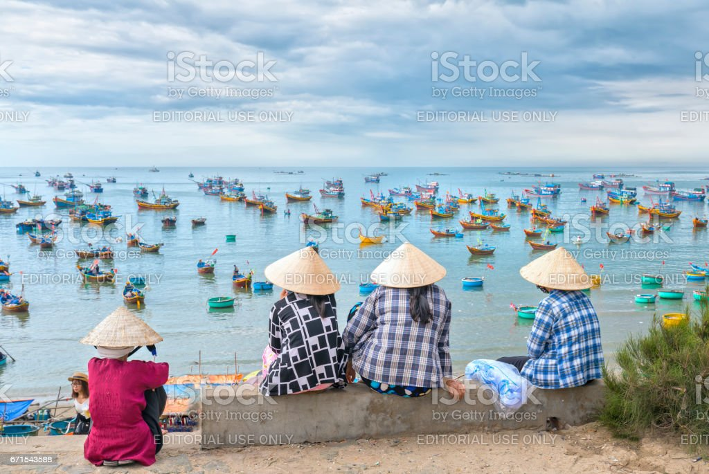 A group of vietnamese women waiting for the fishing boat stock photo
