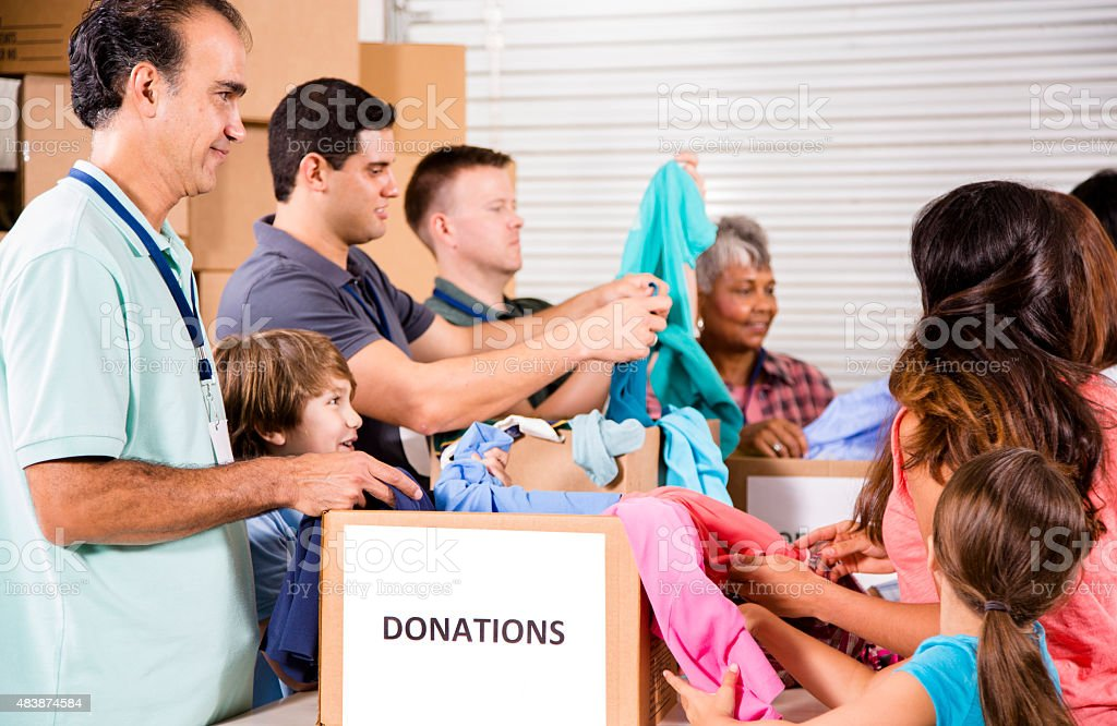 Group of volunteers provide clothing donations to needy families. Charity. stock photo