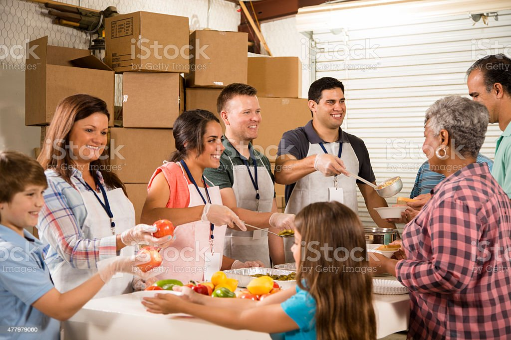 Group of volunteers serve food at community soup kitchen. Charity. stock photo