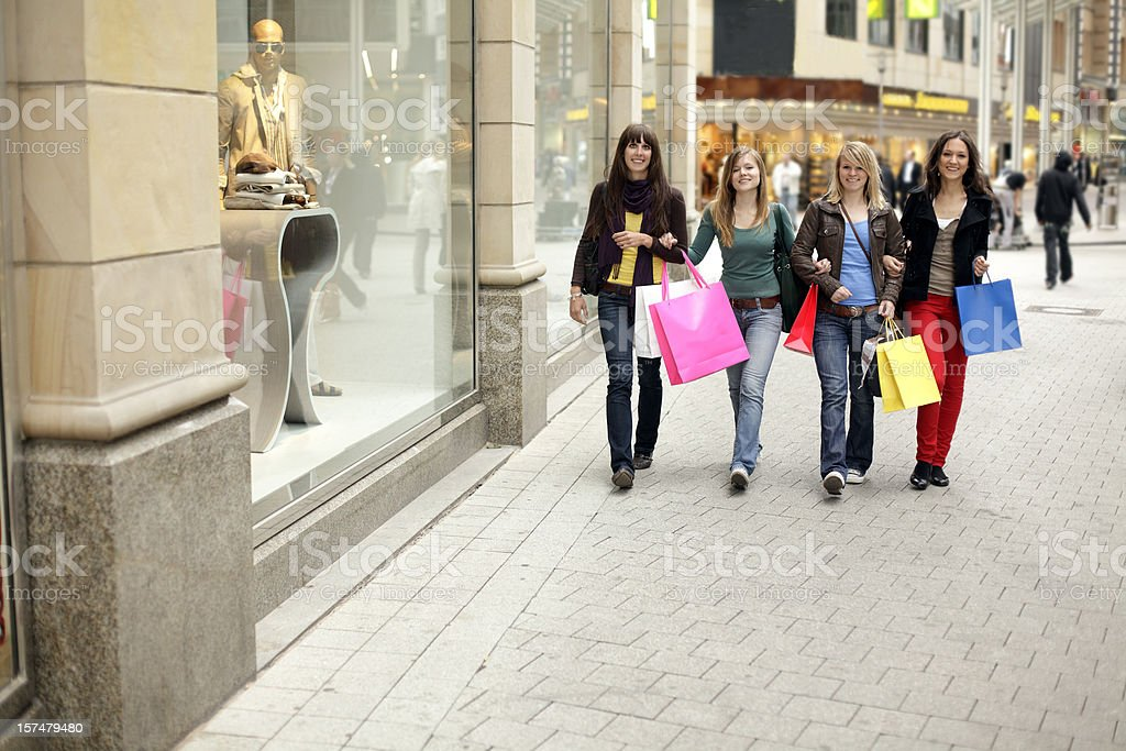 Group of walking young women with multicolored shopping bags (XL) royalty-free stock photo