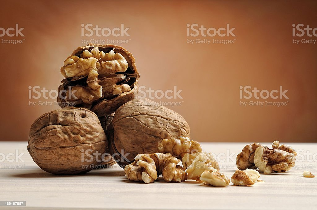group of walnuts on a table with brown background stock photo