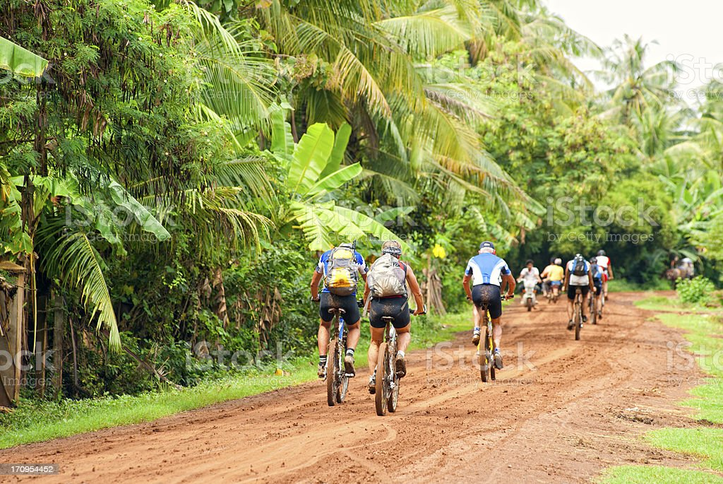Group of Western Mountain Biker at a dirt road, Cambodia royalty-free stock photo