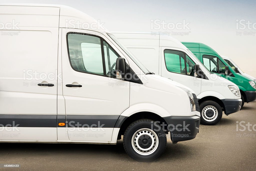Group of white service vehicles parked outdoors stock photo