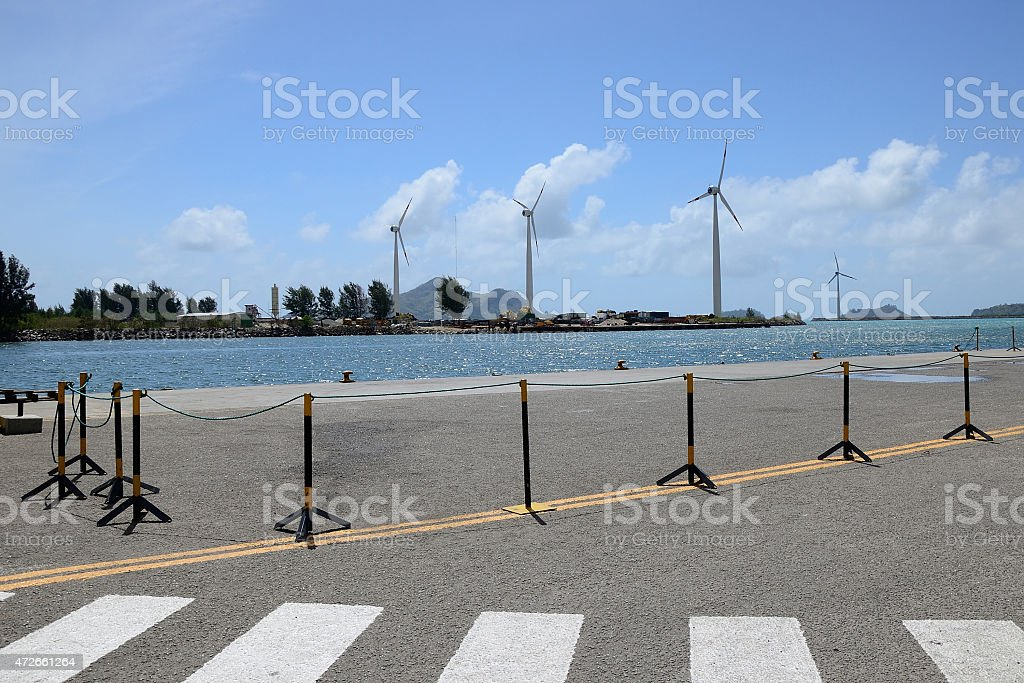 Group of windmills for electric energy production in the port. stock photo