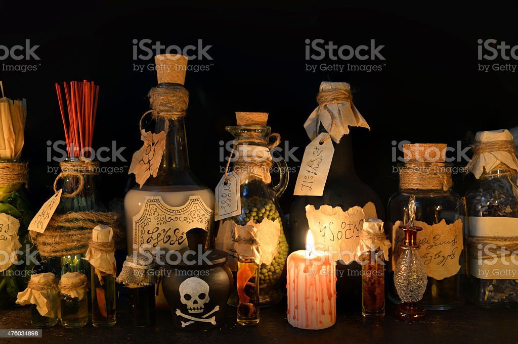 Group of witch magic bottles with candle on black stock photo