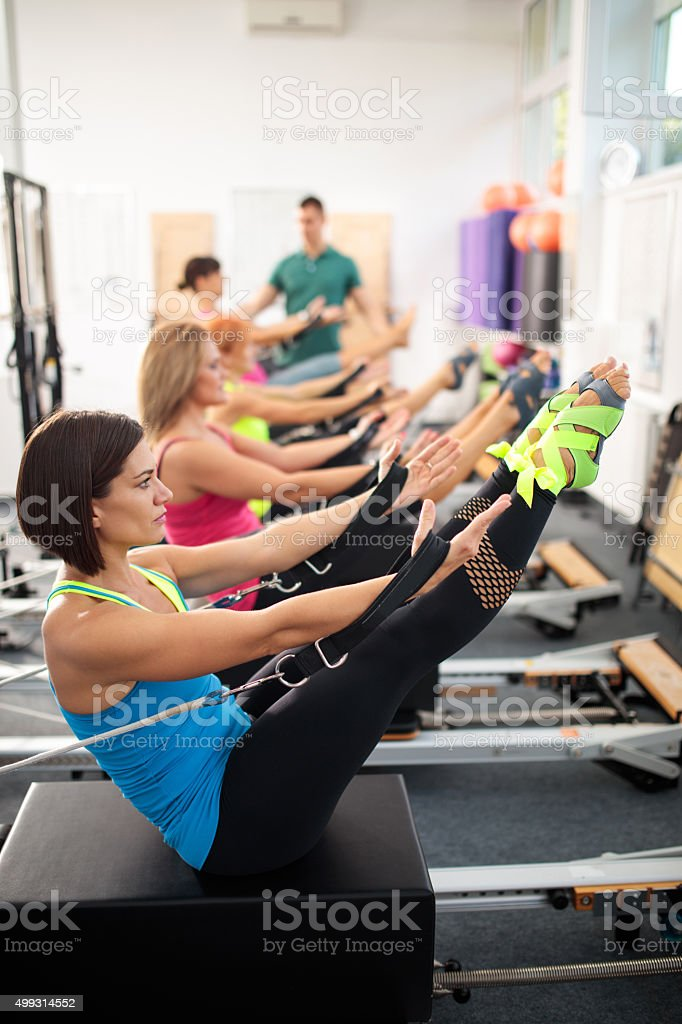 Group of women exercising on Pilates machines in health club. stock photo