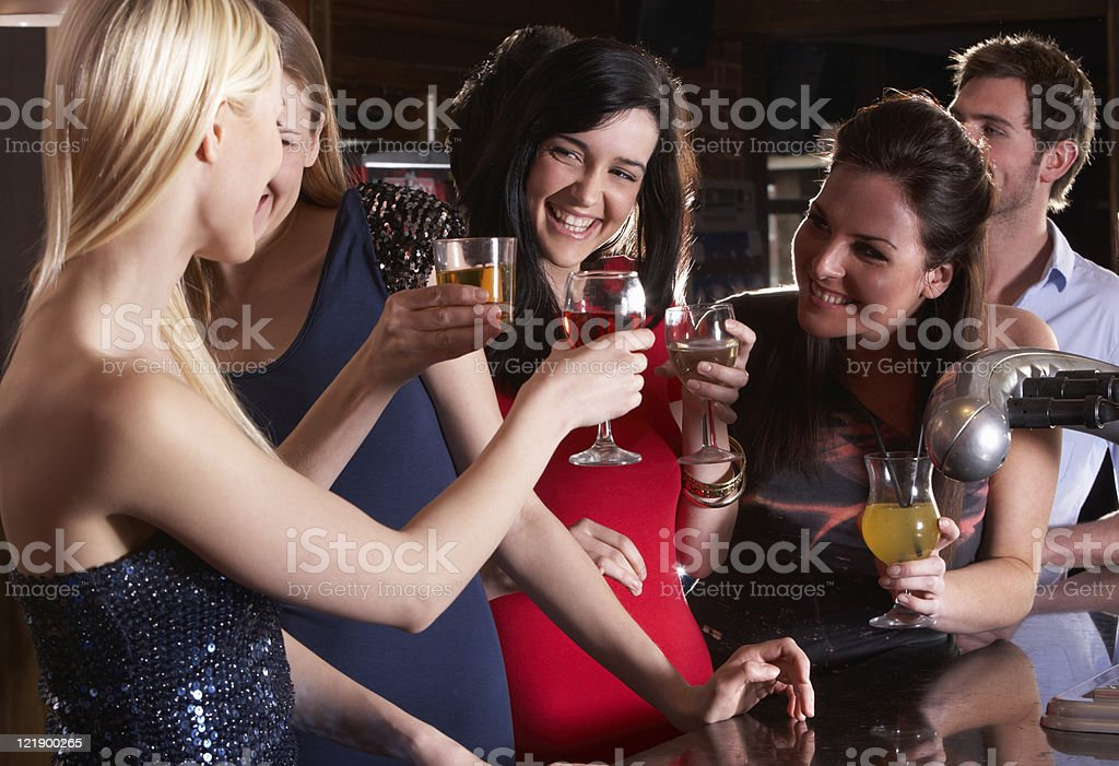 Group of women friends drinking and smiling together stock photo