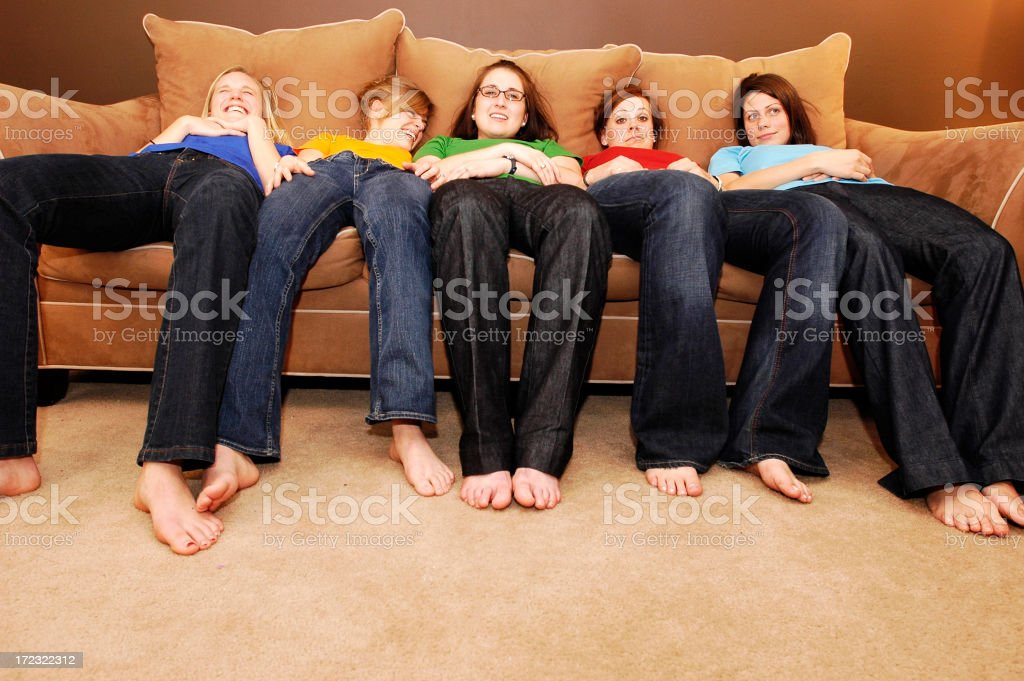 Group of women in colorful shirts lying on giant couch stock photo