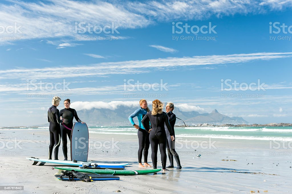 Group Of Women On The Beach With Surf Equipment stock photo