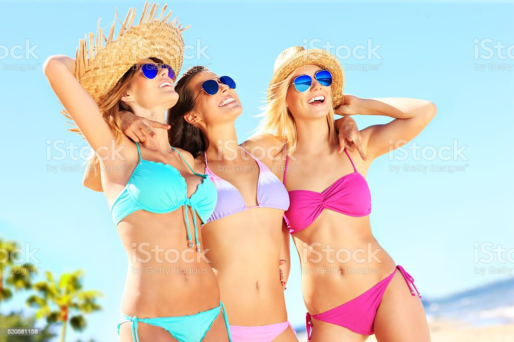Group of women pointing at something on the beach stock photo