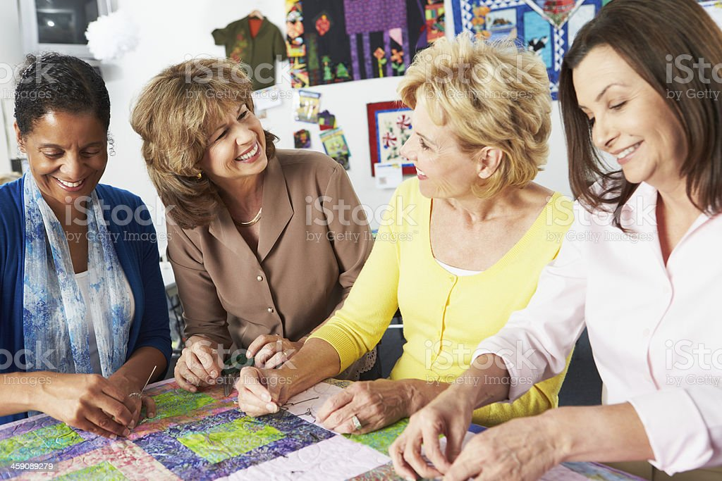 Group of women quilting and smiling together stock photo