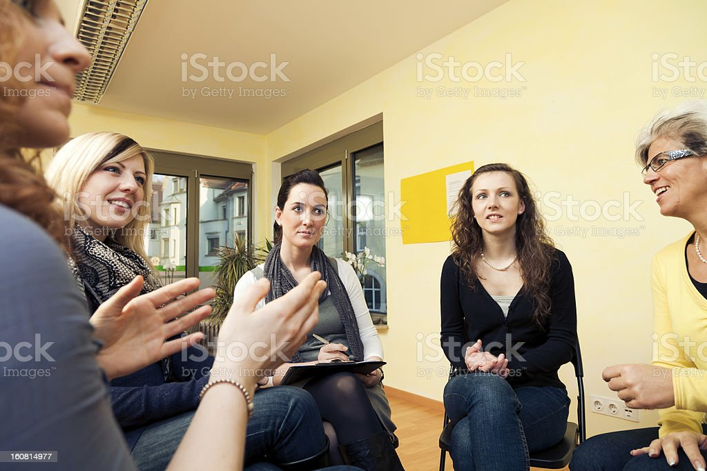 group of women sitting in a circle, discussing royalty-free stock photo
