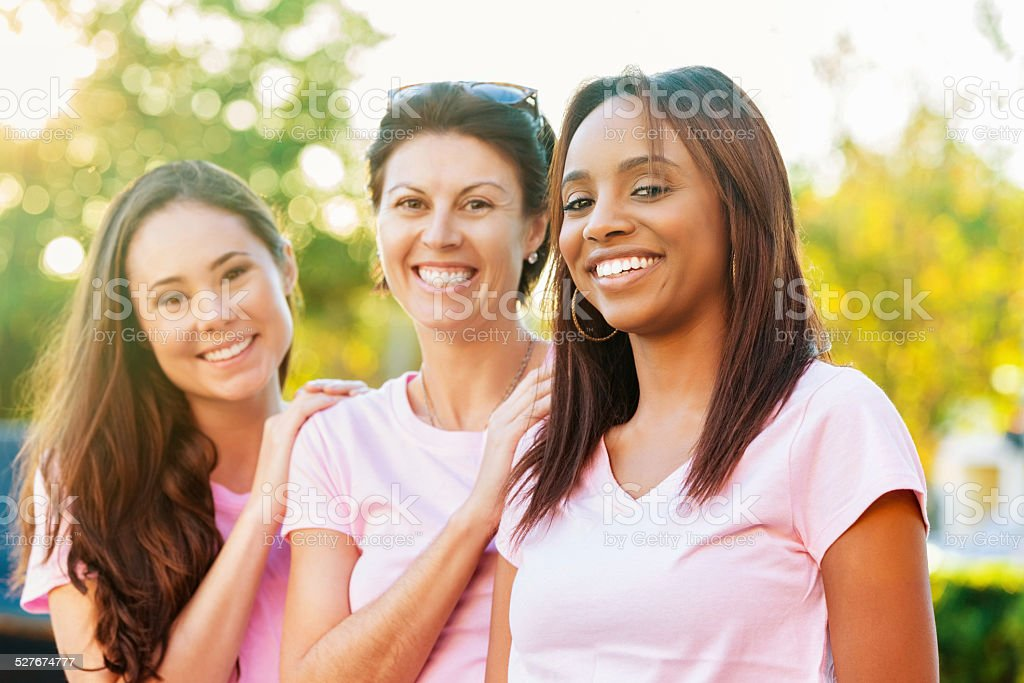 Group of women wearing pink shirts at breast cancer race stock photo