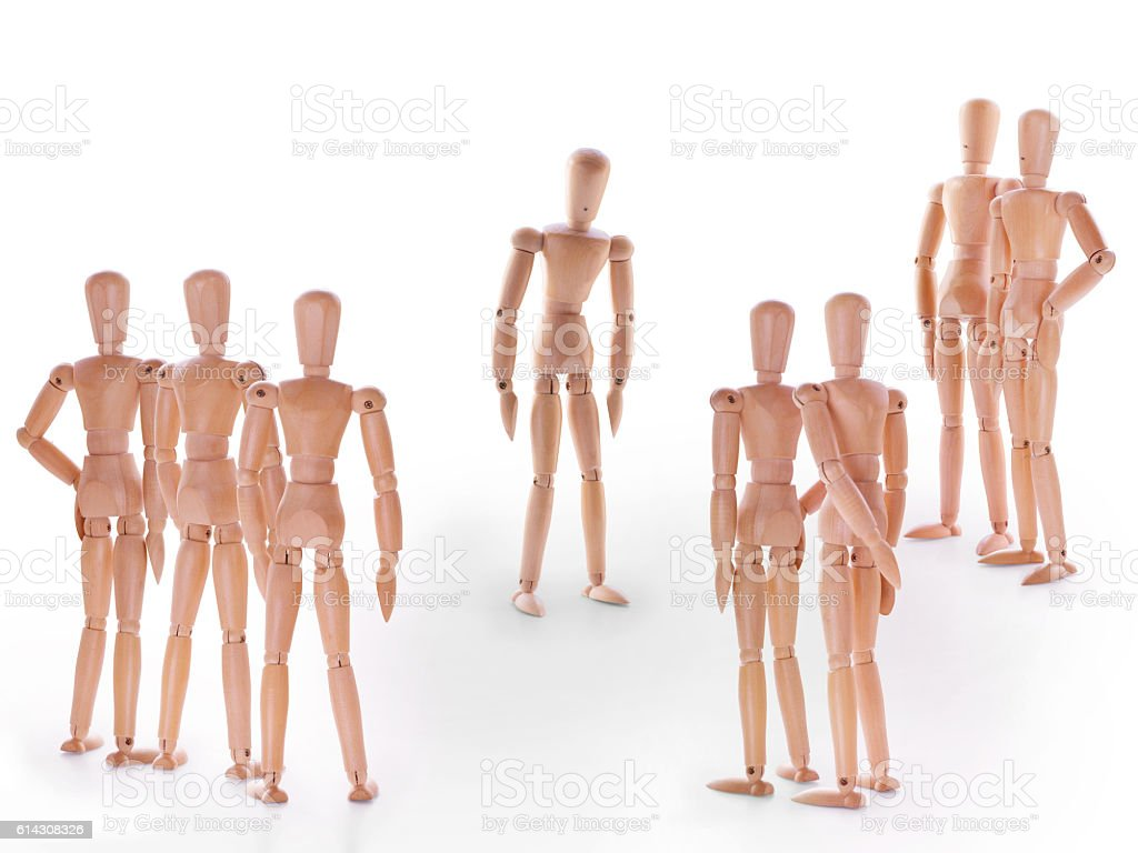 Group of wooden dummy characters standing around one stock photo
