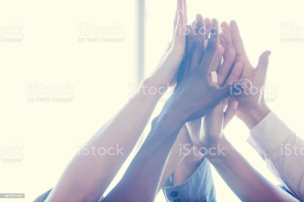 Group of workers high fiving. stock photo