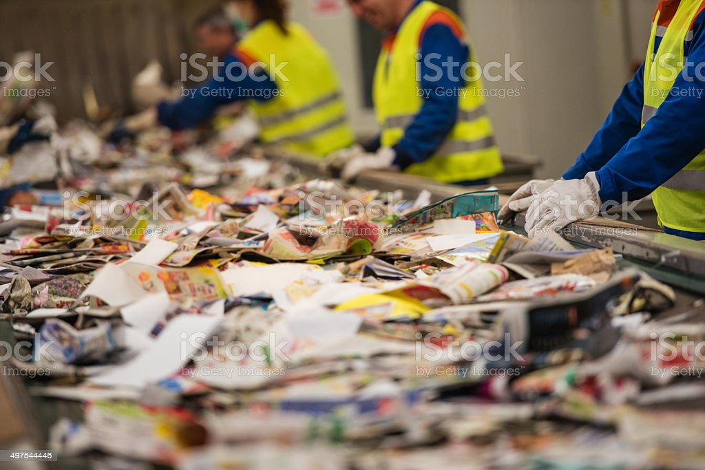 Group of workers sorting papers at recycling plant stock photo