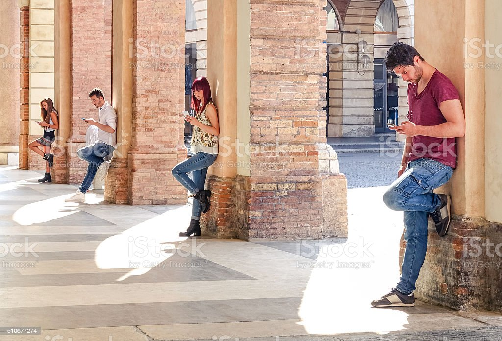 Group of young addicted friends using mobile phones stock photo