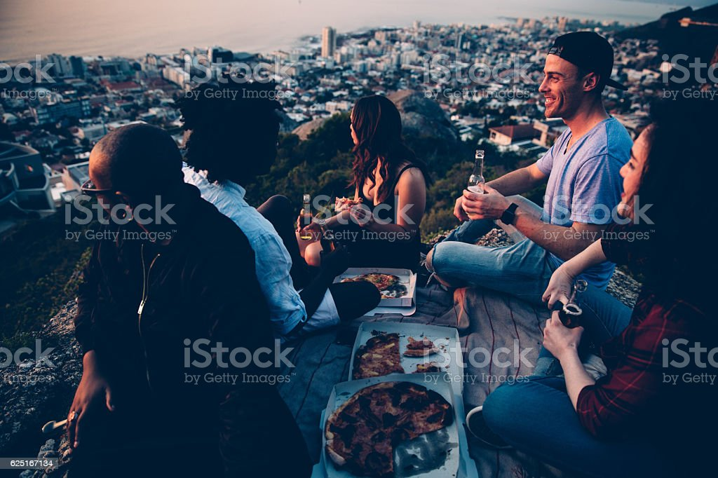 Group of young adult friends having picnic with pizza at stock photo