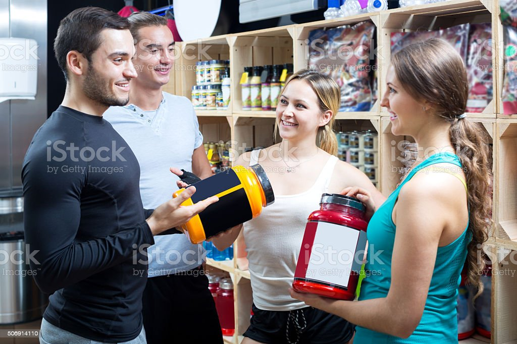Group of young adults discussing bodybuilding supplements stock photo