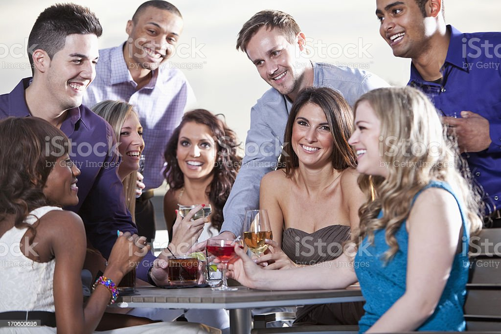 Group of young adults drinking outdoors stock photo
