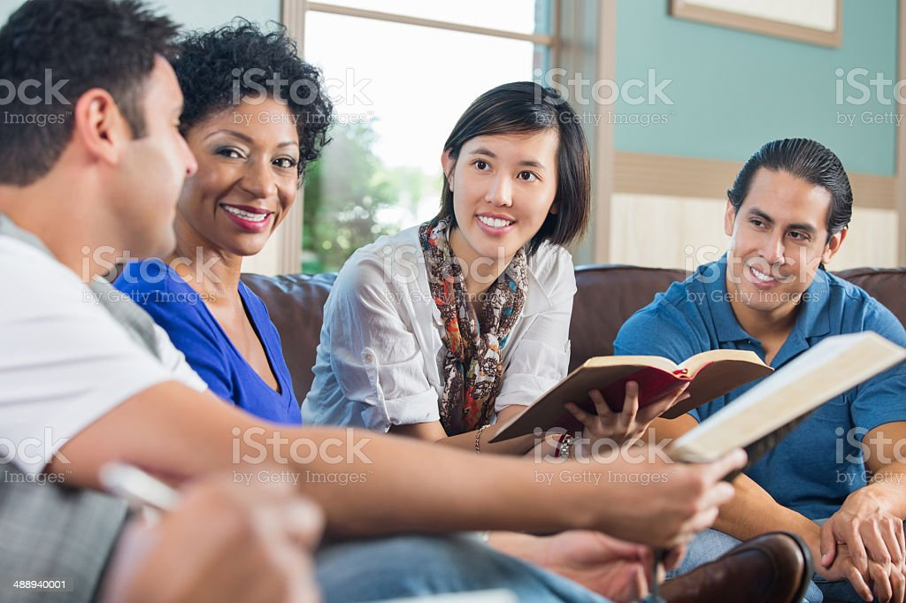 Group of young adults having discussion during bible study stock photo